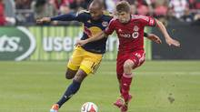 Toronto FC's Nick Hagglund, right, tussles with New York Red Bulls' Thierry Henry during first half MLS soccer action in Toronto on Saturday, May 17, 2014. (Chris Young/THE CANADIAN PRESS)