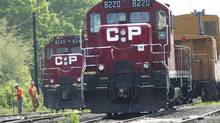 Surveyors work next to CP Rail trains which are parked on the train tracks in Toronto on Wednesday, May 23, 2012. (Nathan Denette/THE CANADIAN PRESS)