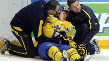 Sweden's Viktor Arvidsson (C) lies on the ice after suffering from injuries during the U20 Premiere World Championship ice hockey match against Canada in Helsinki December 22, 2012. (Jussi Nukari Lehtikuva/Reuters)