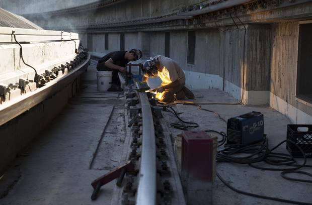 John Gillard, right, welds a rail in the panel one gutter of the Rogers Centre roof, in Toronto on Wednesday, June 24, 2015.