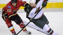 Minnesota Wild's' Kyle Brodziak battles with Calgary Flames' Steve Begin (Larry MacDougal/The Canadian Press)