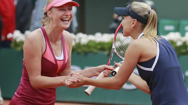 Ekaterina Makarova (L) and Elena Vesnina of Russia celebrate defeating Sara Errani and Roberta Vinci in their women's doubles final match to win the French Open tennis tournament at the Roland Garros stadium in Paris June 9, 2013. (VINCENT KESSLER/REUTERS)