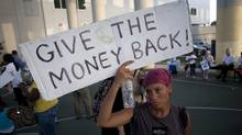 A protester holds a sign during the Occupy Miami protest on Nov. 17. (J Pat Carter/J Pat Carter/Associated Press)