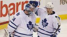 Toronto Maple Leafs netminder James Reimer is congratulated by teammate Carl Gunnarsson (right) following the final whistle as the Leafs defeated the Ottawa Senators 5-3 during NHL pre-season action in Ottawa, Tuesday September 27, 2011. (Adrian Wyld/THE CANADIAN PRESS)