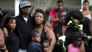 Joseph Bryan(tall in hat), best friend and had attended the party with her, of Shyanne Charles mourns the of 14 year old Charles with his family during a vigil outside an apartment building near her home in Toronto, June 17, 2012, the day after a gun battle took place that left more than 20 people shot including two who were killed while attending a block party on Monday night.