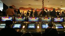 Gamblers play International Game Technology slot machines as a dragon dance is performed to celebrate Chinese New Year in the casino of the Las Vegas Hilton. (SAM MORRIS/REUTERS)