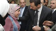 Syria's President Bashar al-Assad speaks to a girl during his visit to the families of students killed during clashes between forces loyal to him and their opponents, in Damascus in this handout photograph released by Syria's national news agency SANA on March 20, 2013. (SANA/REUTERS)