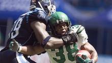 Saskatchewan Roughriders running back Hugh Charles is tackled by Toronto Argonauts defensive end Ronald Flemons (CHRIS YOUNG/THE CANADIAN PRESS)