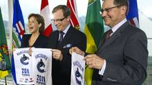 B.C. Premier Christy Clark, left, Sasktachewan Premier Brad Wall, centre, and Alberta Premier Ed Stelmach hold up towels in support of the Vancouver Canucks following a meeting in Vancouver. (ANDY CLARK/Andy Clark/Reuters)