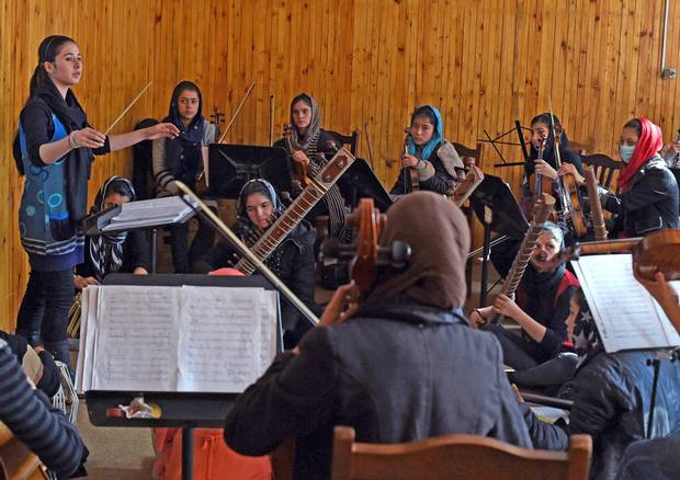 Nineteen year-old Negina Khpalwak, the first female orchestra conductor in Afghanistan, conducts her musicians during a rehearsal at the Afghanistan National Institute of Music in Kabul on Jan. 8, 2018.