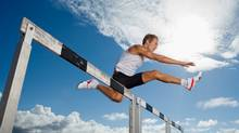 Runner jumping hurdles (Polka Dot Images/Getty Images/Polka Dot RF)