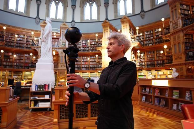 Carleton University professor Stephen Fai adjusts a 360-degree camera in the Library of Parliament.