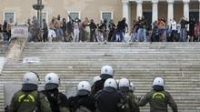 Protesters throw stones at riot police during clashes in front of the parliament in Athens on Tuesday Oct. 9, 2012. German Chancellor Angela Merkel got a hostile reception from Greeks Tuesday when she flew into Athens on her first visit to the country since its debt crisis erupted three years ago. (Nikolas Giakoumidis/AP)
