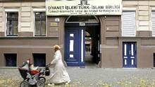 "A Muslim woman wearing a headscarf walks past a Turkish religious organization called the ""Turkish-Islamic Union Institute for Religion"" in Berlin's immigrant-heavy district of Kreuzberg on Sept. 21, 2010. (Sean Gallup/Sean Gallup/Getty Images)"