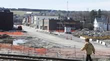 A woman walks the tracks in front of the downtown core in Lac-Mégantic, May 13, 2014. Some residents say Lac-Mégantic's real-estate market is very slow as a result of the derailment. (Christinne Muschi for The Globe and Mail)