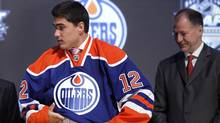 Nail Yakupov puts on his new jersey after being picked by the Edmonton Oilers in the first round of the NHL draft in Pittsburgh on June 22, 2012. (Jason Cohn/REUTERS)