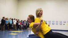 Sydney Lawrie, left, and Georgia Grundmanis do the 'huckle buckle' for Midland Secondary's newcomers. (Michelle Siu for The Globe and Mail)