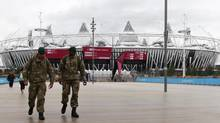 Two soldiers walk through the Olympic Park in east London, July 14, 2012. G4S's failure to provide enough security staff at Olympic venues forced an embarrassed government to draft in soldiers to cover the shortfall. (ANDREW WINNING/REUTERS)