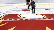 Andrew Higgins sprays down the Calgary Flames logo as work continues at the home of the Flames in Calgary, Alta., Thursday, Sept. 5, 2013. Severe flooding damaged the arena last June. (Jeff McIntosh/THE CANADIAN PRESS)