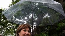 B.C. Premier and Liberal Leader Christy Clark uses an umbrella as she walks into a coffee shop for a campaign stop in Oak Bay, B.C., on Monday May 13, 2013. British Columbians go to the polls Tuesday for a provincial election. (DARRYL DYCK/THE CANADIAN PRESS)
