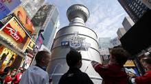 Young hockey fans drink water from a giant water fountain in the shape of the Stanley Cup, presented to the champions of the National Hockey League stands on display in Times Square, New York April 11, 2012. (PHIL NOBLE/REUTERS)