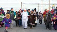 Torchbearer Terry Kuliktana is seen carrying the Olympic Flame through Kugluktuk, NU., on Nov. 5. (Jonathan Hayward/Jonathan Hayward/CP)