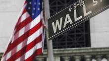 The American flag and Wall St. street sign outside the New York Stock Exchange in New York in this July 15, 2013 file photo. (MARK LENNIHAN/THE ASSOCIATED PRESS)