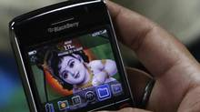 A customer checks the features of a Blackberry handset at a mobile showroom in New Delhi August 30, 2010. (ADNAN ABIDI/REUTERS)