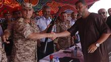 A Libyan man hands over his weapon to Libyan army chief of staff Yussef al-Mangoush in Tripoli's Martyrs Square on Saturday. (ISMAIL ZITOUNY/REUTERS)