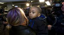 A tired four year old Angelo Epassa looks away as mom Nathalie Epassa talks to the media as they arrive home in Toronto on January 6, 2014, after the boy was missing for the day. (Deborah Baic/The Globe and Mail)