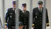 Cpl. Matthew Wilcox, the 24-year-old soldier from Glace Bay, N.S., who was convicted in July of criminal negligence causing death and neglect of duty, is framed by a railing as he is escorted from his sentencing hearing in Sydney, N.S. on Friday, Sept. 11, 2009. (ANDREW VAUGHAN)