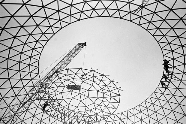 Workmen wait on dome for crane to finish maneouvring the cap of Cinesphere into position, Oct. 26, 1970.