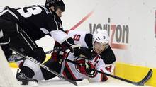 Los Angeles Kings' Willie Mitchell, left, and New Jersey Devils' Zach Parise struggle to control the puck in the first period during Game 4 of the NHL hockey Stanley Cup finals, Wednesday, June 6, 2012, in Los Angeles. (The Canadian Press)