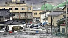 An earthquake-triggered tsunami washes away a warehouse and vehicles in Kesennuma, Miyagi prefecture, Japan, Friday March 11, 2011. (Yomiuri Shimbun/Associated Press/Yomiuri Shimbun/Associated Press)