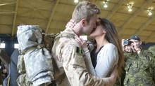MCpl Anthony Alliot and Sarah Tooth kiss after the last Canadian troops from Afghanistan returned toOttawa on Tuesday, March 18, 2014. (Adrian Wyld/The Canadian Press)