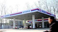 A cyclist rides past a gas station of CNOOC (China National Offshore Oil Corporation) in Zhoukou city, central Chinas Henan province, in this file photo. (The Canadian Press)