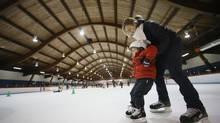 Yanick Chevrier-Bedard helps son Robin, 2, out for his first skate at the Eric Sharp Arena in Saint-Lambert, Que., on Dec. 14, 2013. (CHRISTINNE MUSCHI FOR THE GLOBE AND MAIL)