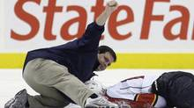 "In this Oct. 24, 2009, file photo, a person signals to the bench after checking on Florida Panthers forward David Booth, who was injured in the second period of an NHL hockey game against the Philadelphia Flyers in Philadelphia. The NHL's new rule banning blindside hits to the head is called ""Rule 48. It easily could be named after victims David Booth and Marc Savard, or offenders Mike Richards and Matt Cooke, who might be the last players to get away with such shots unscathed. For the first time, a lateral or blindside hit on an opponent in which the head is targeted or is the main area of impact will not only be subject to supplemental discipline, but a major penalty and ejection from the game. (AP Photo/Matt Slocum, File) (Matt Slocum)"
