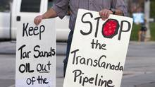 In this Sept. 21, 2010 photo, an unidentified protester who is opposed to the Keystone XL pipeline because of environmental reasons, carries signs in Omaha, Neb. (Nati Harnik/Nati Harnik/THE CANADIAN PRESS)