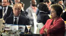 Russian President Vladimir Putin and Brazilian President Dilma Rousseff listen to an orator Tuesday during their meeting in Durban, South Africa. (Alexei Druzhinin/AP)