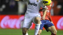 Real Madrid's Xabi Alonso, left, duels for the ball with Osasuna's Alvaro Cejudo, during their Spanish League soccer match, at Reyno de Navarra stadium in Pamplona, Spain, Saturday. (Alvaro Barrientos/AP)
