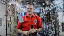 Astronaut Chris Hadfield poses for a photo with a new polymer $5 bank note on the International Space Station as seen via video link in Ottawa on April 30, 2013. Retired Canadian astronaut Chris Hadfield is calling for more co-operation with China in space and he wants it to be part of any international effort to return to the moon. (Sean Kilpatrick/THE CANADIAN PRESS)