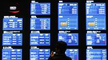 A man takes a photo of displays showing market prices at the Tokyo Stock Exchange in Tokyo April 11, 2012. (Toru Hanai/Toru Hanai/REUTERS)