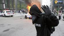 A G20 protester passes a burning police cruiser in downtown Toronto on June 26. (Frank Gunn/The Canadian Press/Frank Gunn/The Canadian Press)