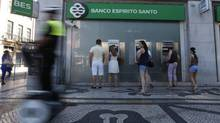 People use automated teller machines (ATMs) of Portuguese bank Banco Espirito Santo in downtown Lisbon July 11, 2014. (RAFAEL MARCHANTE/REUTERS)