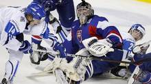 Team Finland's Roope Hamalainen, left, scores on Team Slovakia's goalie Juraj Simboch, centre, during first period IIHF World Junior Championships quarter-final hockey action in Calgary, Alta., Monday, Jan. 2, 2012.THE CANADIAN PRESS/Jeff McIntosh (Jeff McIntosh/CP)