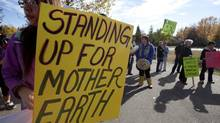 Demonstrators stand outside the Joint Review Panel looking into the Northern Gateway Pipeline in Prince George, B.C. on Oct. 9, 2012. (JONATHAN HAYWARD/THE CANADIAN PRESS)