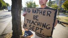 Oliver Reedman, 3, walks the picket line Tuesday with his dad Nigel outside of Vancouver where he teaches at Technical Secondary School. (John Lehmann/The Globe and Mail)