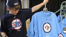 Winnipeg Jets fan Matthew Sawka holds a t-shirt with the NHL team's new logo in Winnipeg, July 22, 2011. REUTERS/Fred Greenslade (Fred Greenslade/Reuters)