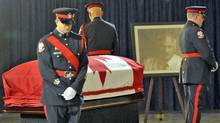A police honour guard stands watch by the casket of Opposition Leader Jack Layton at Toronto City Hall on Aug. 25, 2011. (J.P. MOCZULSKI/J.P. MOCZULSKI for The Globe and Mail)